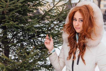 Winter fashion. Portrait of a beautiful red hair young woman in warm clothes outdoor near the pine tree. Stock Photo