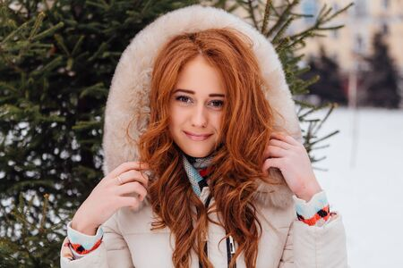 european white birch: Winter fashion. Portrait of a beautiful red hair young woman in warm clothes outdoor near the pine tree. Stock Photo