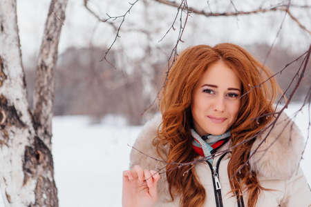 Winter fashion. Portrait of a beautiful red hair young woman in warm clothes outdoor near the birch tree. Stock Photo
