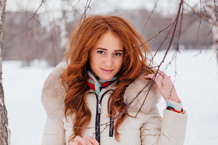european white birch: Winter fashion. Portrait of a beautiful red hair young woman in warm clothes outdoor near the birch tree. Stock Photo