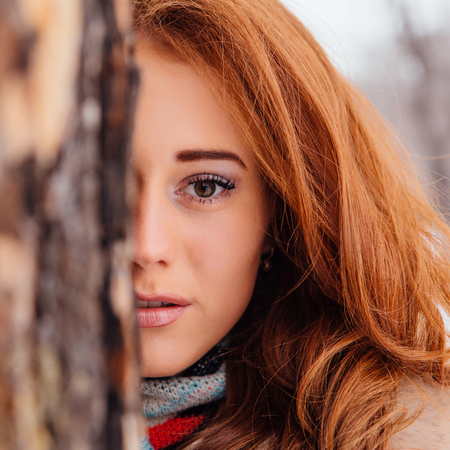 Winter fashion. Half face square portrait of a beautiful red hair young woman in warm clothes outdoor near the tree. Stock Photo