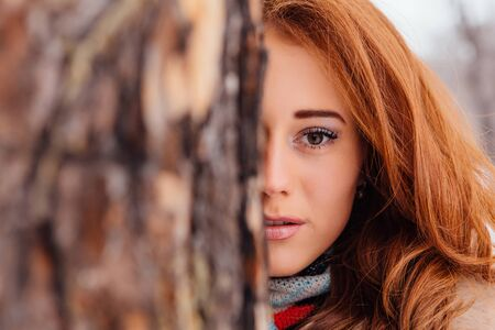 european white birch: Winter fashion. Half face portrait of a beautiful red hair young woman in warm clothes outdoor near the tree.