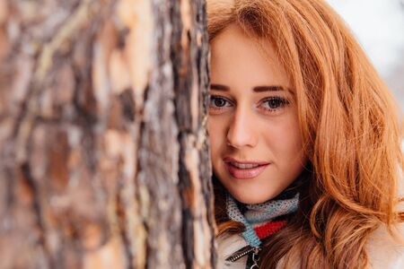 Winter fashion. Portrait of a beautiful red hair young woman in warm clothes outdoor near the tree.