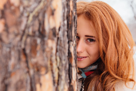 european white birch: Winter fashion. Portrait of a beautiful red hair young woman in warm clothes outdoor near the tree.