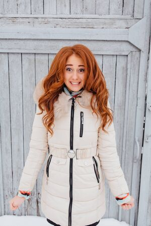 european white birch: Portrait of a beautiful red hair young woman in warm clothes outdoor on the grey wooden background. Girl shows different emotions.