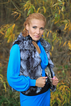 Outdoor Fashion image of a woman in fur vest. Stock Photo
