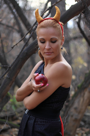 Woman in the forest with devil horns holds red apple.