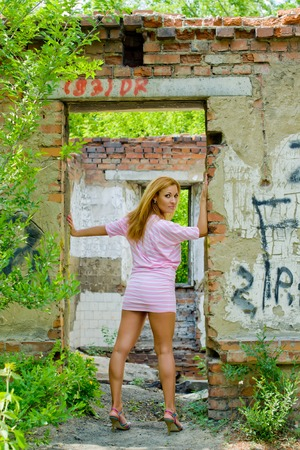 Modern young woman stands in doorway of an old broken house.