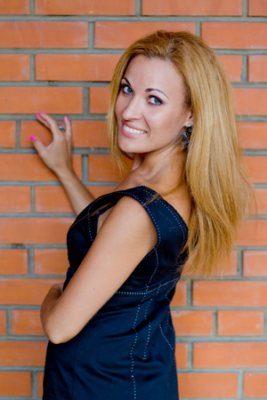 Young red hair woman near the brick wall.