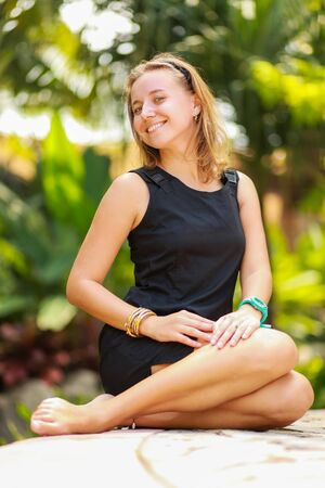 calm woman: Outdoor summer portrait of young beautiful girl with blond hair posing in short black stylish dress in tropical park Stock Photo