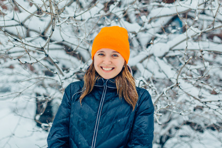european white birch: Winter fashion. Portrait of a smiling red hair young woman in warm clothes outdoor.