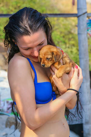 baby girls smiley face: Chonburi, Thailand - February 01, 2015 :: Young woman hugging little brown dog on the beach.
