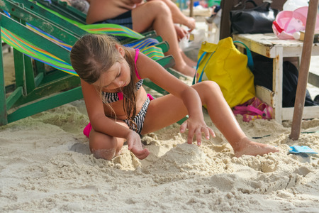 december 25: Koh Samed, Rayong, Thailand - December 25, 2014 :: Adorable girl playing with sand on tropical beach