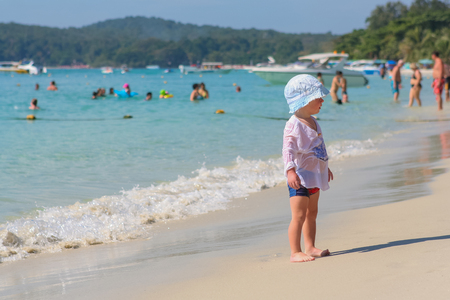 december 25: Koh Samed, Rayong, Thailand - December 25, 2014 :: Little kid in white hat playing on the beach near blue sea