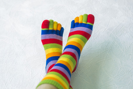 barefoot people: Close-up photo of the woman legs in zebrine socks on the white background Stock Photo