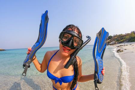 flippers: mujer joven con máscara de buceo y aletas en el fondo hermoso mar