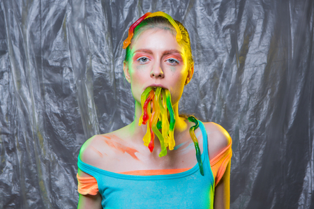 worm snake: Young woman with colorful make up holds gummy jelly worms candies in mouth.