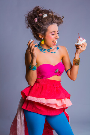 durty: Beautiful girl in bright clothes and make up eats chokolate creamy muffin with cherry