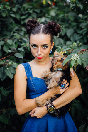 green life: Young beautiful woman with Yorkshire Terrier near green bush