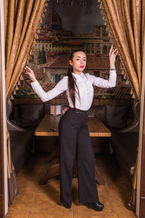 restaurateur: Young gorgeous businesswoman standing and posing in restaurant interior.