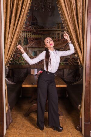 Young gorgeous businesswoman standing and posing in restaurant interior.