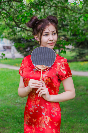 chinese fan: Beautiful asian girl in traditional chinese red dress with fan in hands near blooming apple tree in the park. Stock Photo