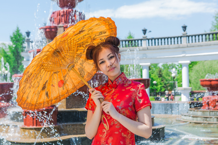 bamboo fountain: Beautiful asian girl in traditional chinese red dress with bamboo umbrella near fountain