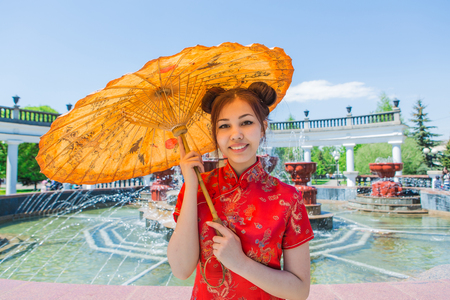 Beautiful asian girl in traditional chinese red dress with bamboo umbrella near fountain