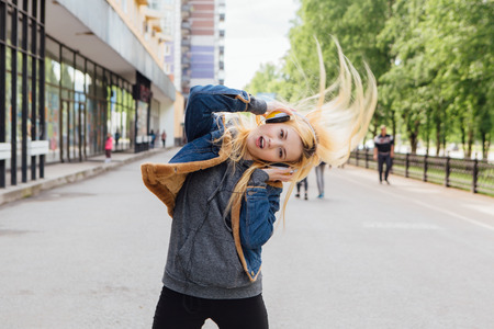 radio active: Girl listening to music streaming with headphones and dancing on the street. Stock Photo