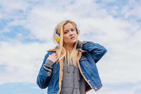 radio active: Girl listening to music streaming with headphones and dancing on sky background