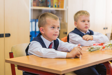 sep: NOVOKUZNETSK, KEMEROVO REGION, RUSSIA - SEP, 1, 2016: First-grade students and teacher are in school classroom at first lesson. The day of knowledge in Russia.
