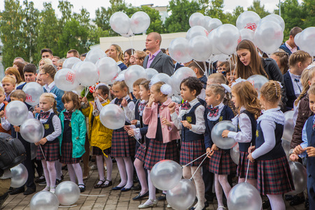 schoolyard: NOVOKUZNETSK, KEMEROVO REGION, RUSSIA - SEP, 1, 2016: Meeting with the first-grade pupils and teacher at schoolyard. The day of knowledge in Russia.