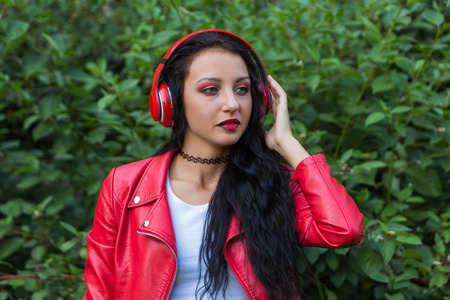 gree: Girl in red jacket listening to music streaming with headphones on the gree background. Close up portrait.
