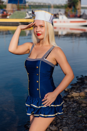 Young retro pinup girl wearing sailor uniform on the river shore Banque d'images