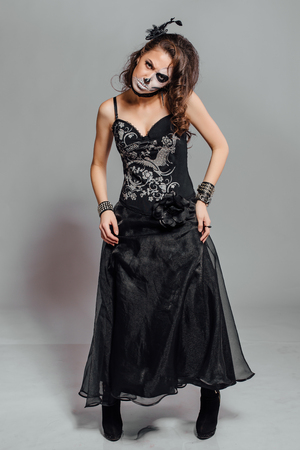 skeleton costume: Young woman in black with half face skull make-up. Stock Photo