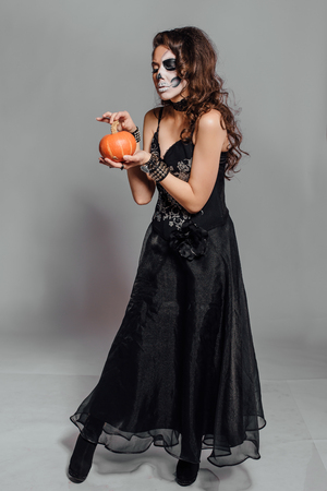 skeleton costume: Young woman in black with half face skull make-up and pumpkin in hand.