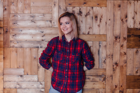 Pretty hipster girl near the wooden wall in loft style room