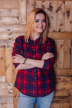 sudio: Pretty hipster girl near the wooden wall in loft style room