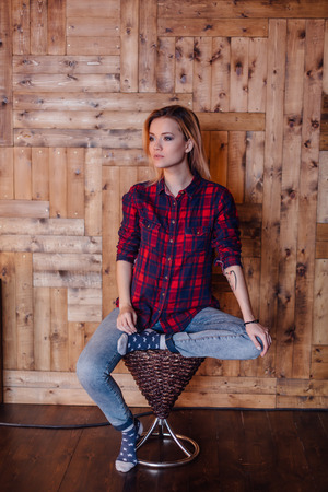 sudio: Pretty hipster girl siiting on the chair near the wooden wall in loft style room