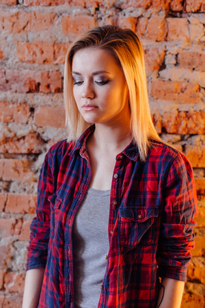 domicile: Pretty hipster girl near the brick wall in loft style room