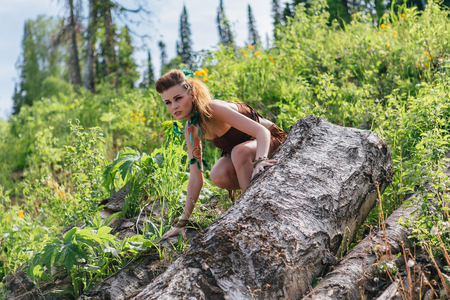 Young and beautiful savage girl in forest Stock Photo
