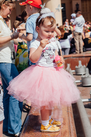 selebration: NOKUZNETSK, KEMEROVO REGION, RUSSIA - JUNE 01, 2012 :: Childrens protection day. Soup bubbles day selebration. Cute Little girl is blowing soap bubbles