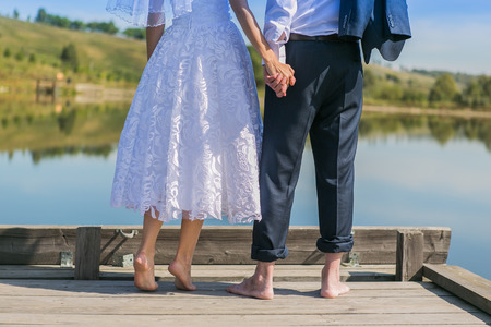 standing together: Bare feet of groom and bride standing close to each other near the lake Stock Photo