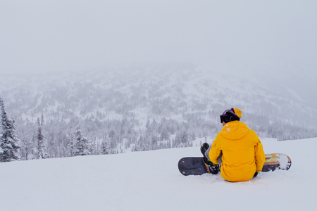 piste: Snowboarder seats on the top of mountain preparing to ride. Stock Photo
