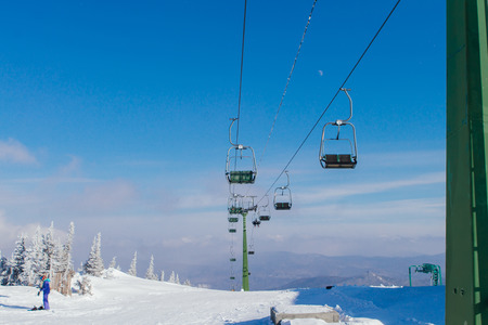 Ski lift and chairs on snowy slope
