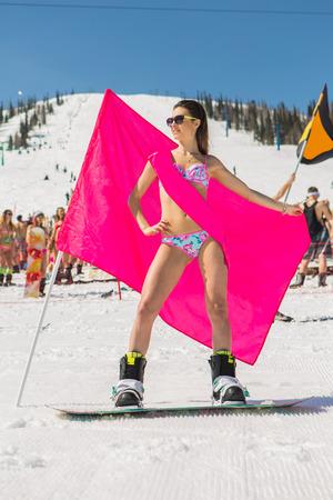 A slender girl in in bikini on the snowboard holding pink flag