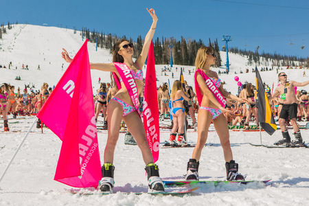 Sheregesh, Kemerovo region, Russia - April 16, 2016: Grelka Fest is a sports and entertainment activity for ski and snowboard riders in bikini in Russia, Sheregesh. Group of young happy pretty women on a snowboard in colorful bikini with flags.