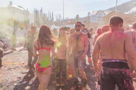 Sheregesh, Kemerovo region, Russia - April 16, 2016: Grelka Fest is a sports and entertainment activity for ski and snowboard riders in bikini. A group of a young people throwing colorful holi powder.