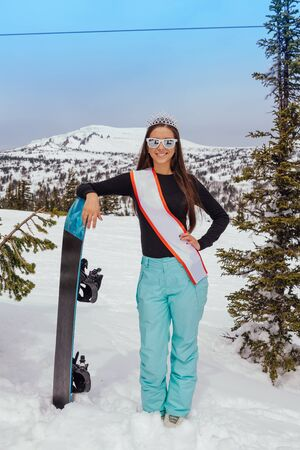 Beautiful snowboard girl with a crown on the head standing on the top of the mountain holding snowboard. Queen of snowboard. Winner of a beauty contest.