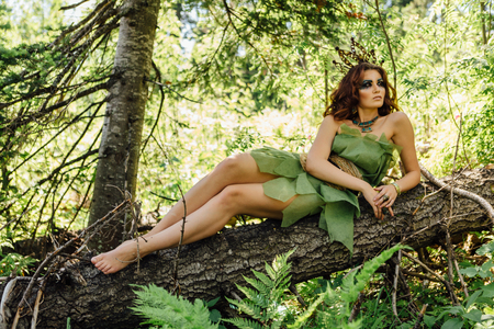 Portrait of a fairy princess laying on the tree in the summer forest